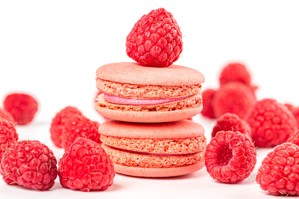 Dessert pink macaroons with raspberries on white background