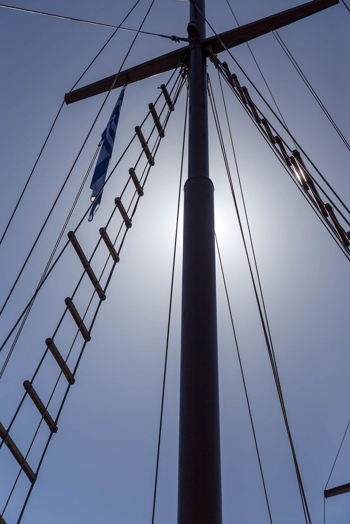 Detail eines Segelbootmasts mit griechischer Flagge von unten gesehen