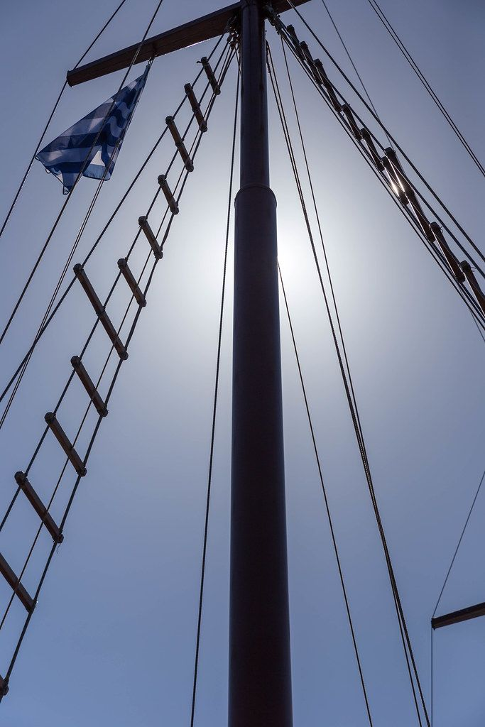 Detail of a sailboat with Greek flag and the sun hidden behind the mast, seen from below