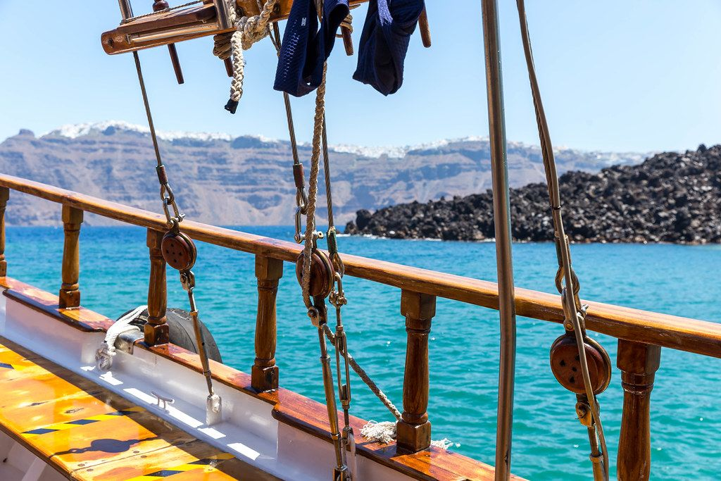 Details of a sailboat off the volcanic coast of Santorini with blue sea on a sunny day