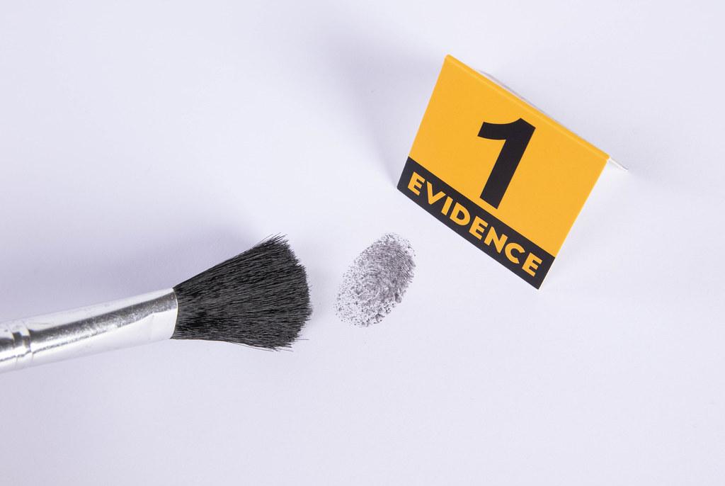 Detective using powder and brush to take fingerprint