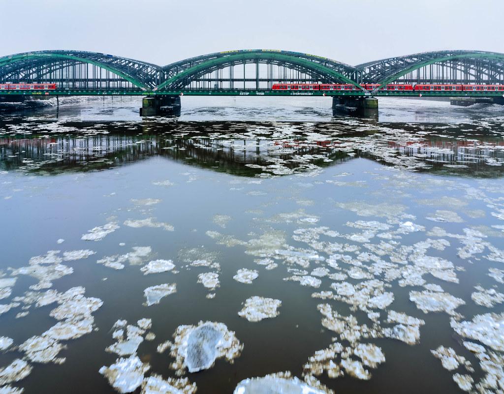 Deutsche Bahn trains crossing Hamburg bridge in the winter with ice floes flowing beneath in Elbe river