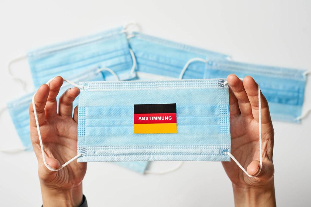 Deutsche Flagge mit Abstimmungstext auf medizinischer Gesichtsmaske