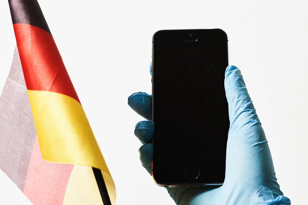 Deutsche Flagge und Hand mit Smartphone und Einweghandschuh vor weißem Hintergrund