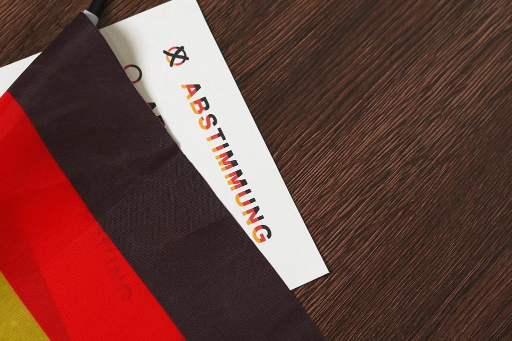 """Deutsche Flagge und Zettel mit Schrift """"Abstimmung"""" in Schwarz-Rot-Gold vor hölzernem Hintergrund"""