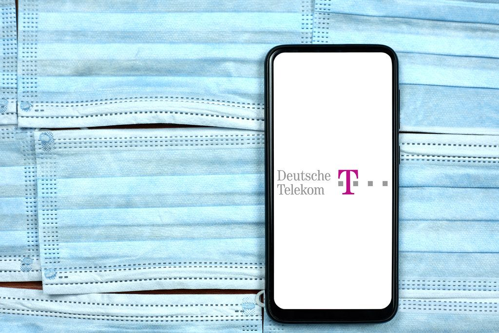 Deutsche Telekom logo on smartphone screen over the face masks. Global company during coronavirus crisis
