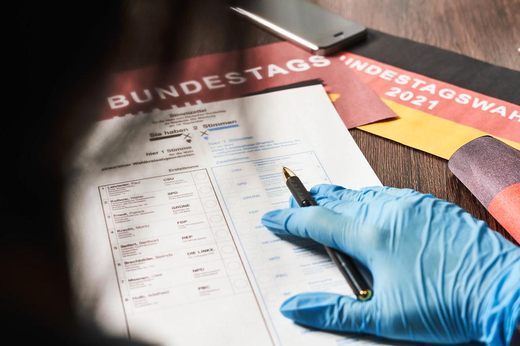 Deutsche Wählerin mit Einweghandschuh vor dem Stimmzettel für die Bundestagswahl 2021