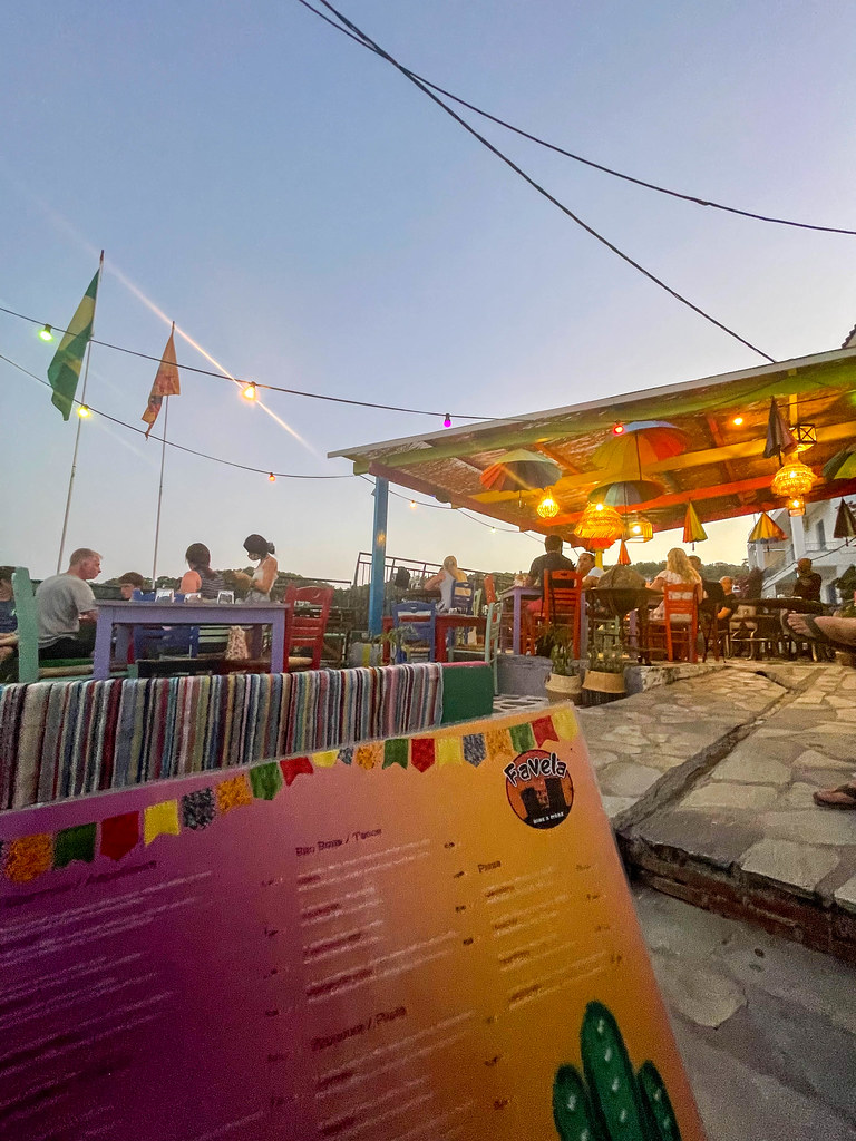 Die bunte Einrichtung mit regenbogenfarbene Sonnenschirme beim Restaurant Favela in Patitiri auf Alonnisos