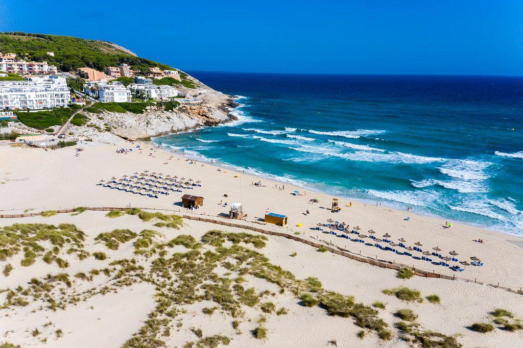 Die Dünen und der Strand von Cala Mesquita auf Mallorca mit Strandschirmen aus Stroh. Luftbild