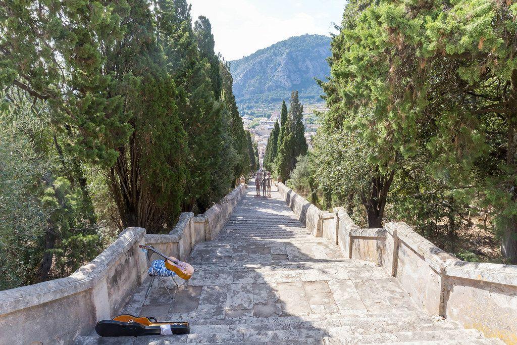 Die Freitreppe Carrer del Calvari in Pollença mit Skulpturen und der Gitarre eines Straßenmusikers