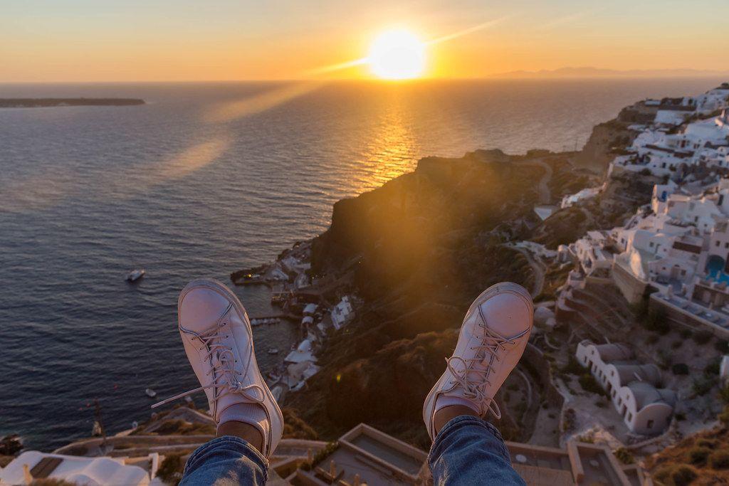Die Füße eines Mannes, der den Sonnenuntergang beobachtet und die Aussicht auf Santorin genießt