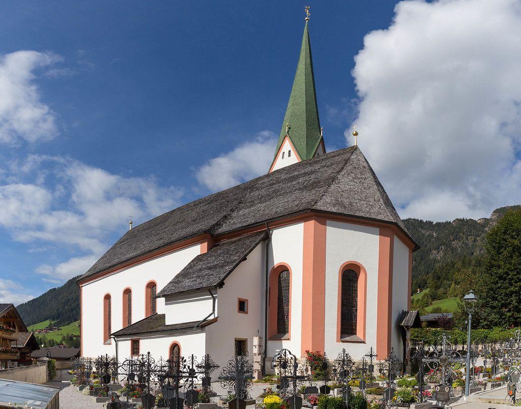 Die Katholische Pfarrkirche hl. Oswald in Alpbach (Tirol) mit Kirchturm und Friedhof