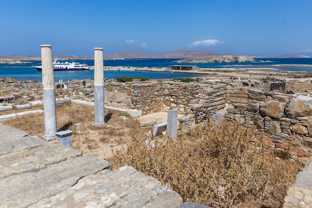 Die Ruinen von Delos Theater-Viertel mit blauem Meer und Fähre im Hintergrund