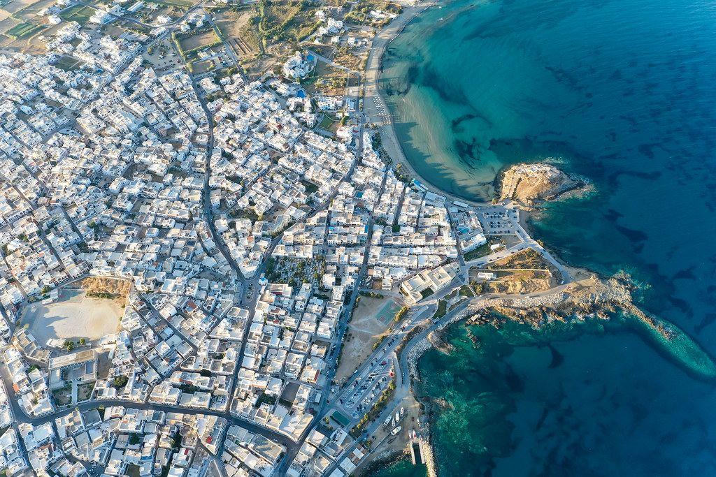 Die Stadt Naxos oder Chora mit weißen Gebäuden und dem Agios Georgios Strand. Luftaufnahme