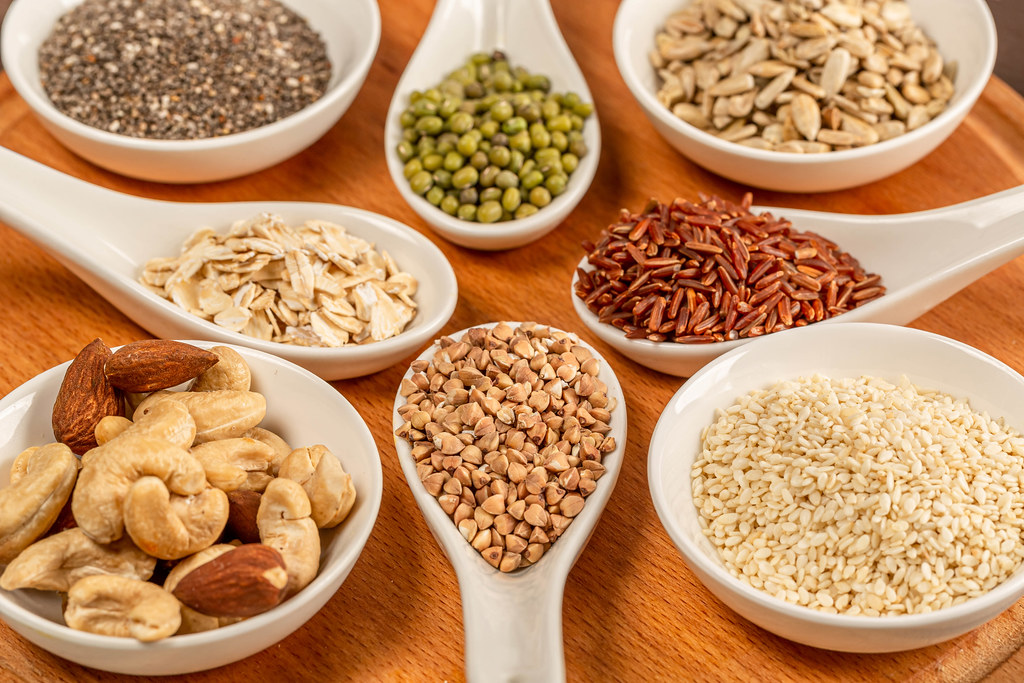 Diet cereals, seeds and nuts on a wooden background, close-up
