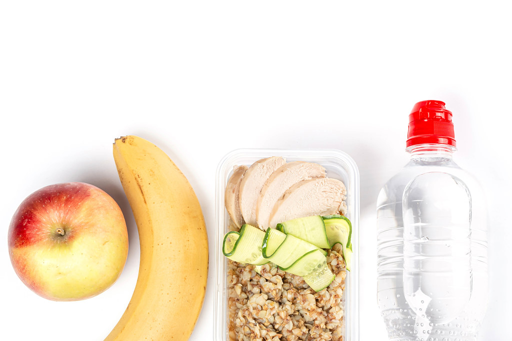 Diet food on a white background, fresh vegetables and fruits, buckwheat, chicken and water in bottle