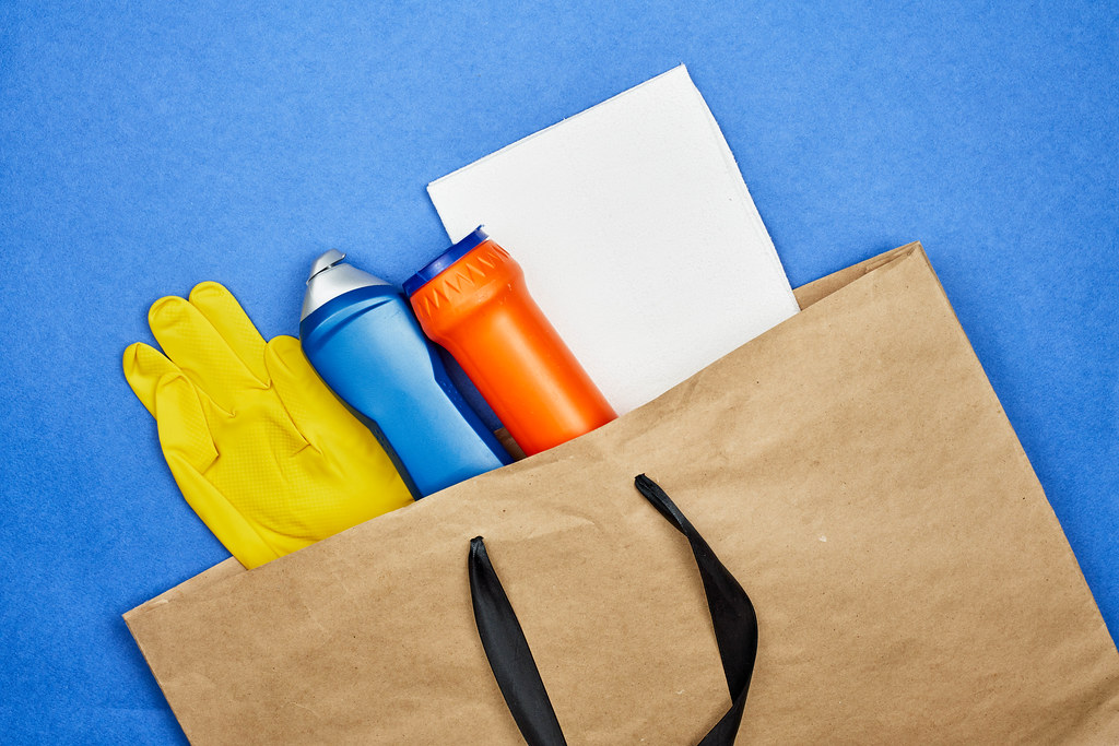 Different cleaning products in shopping bag. Buy cleaning supplies