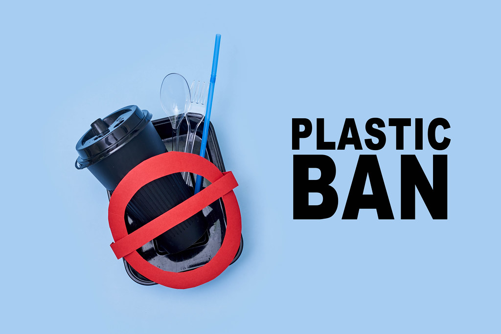 Different plastic items and red restriction sign with text - Plastic ban