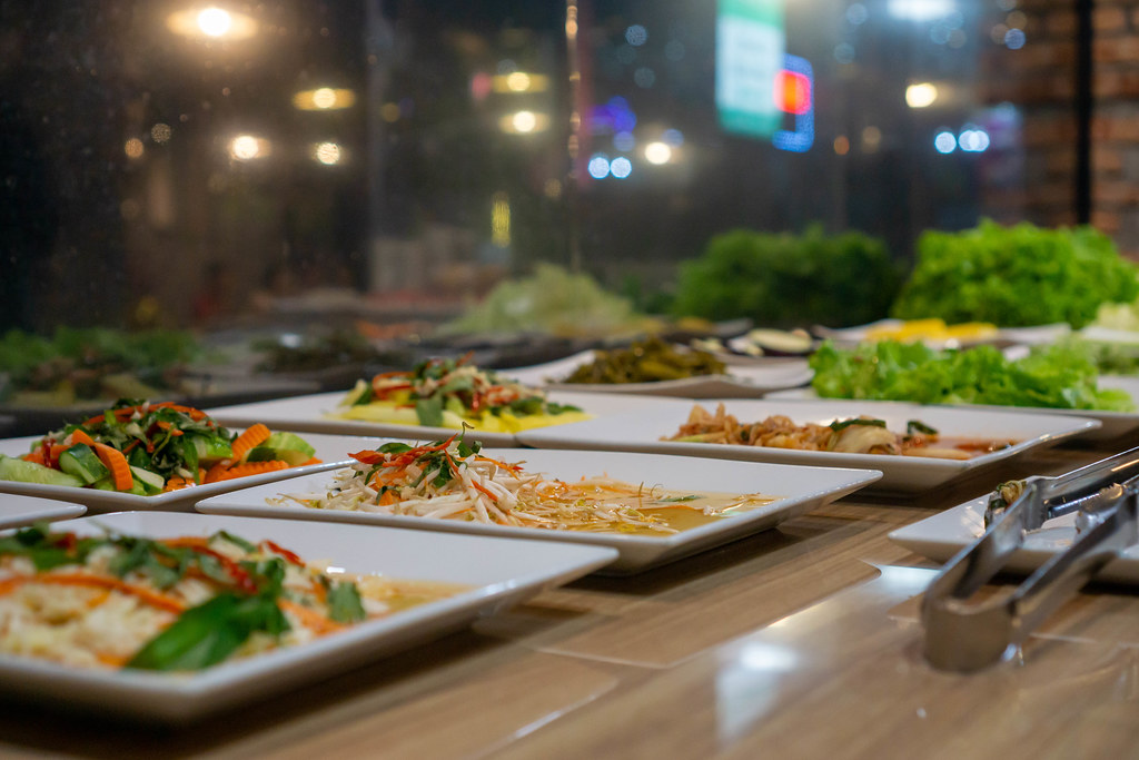 Different Salads, Stir Fried Vegetables and Raw Vegetables on Plates at a Buffet inside a Restaurant