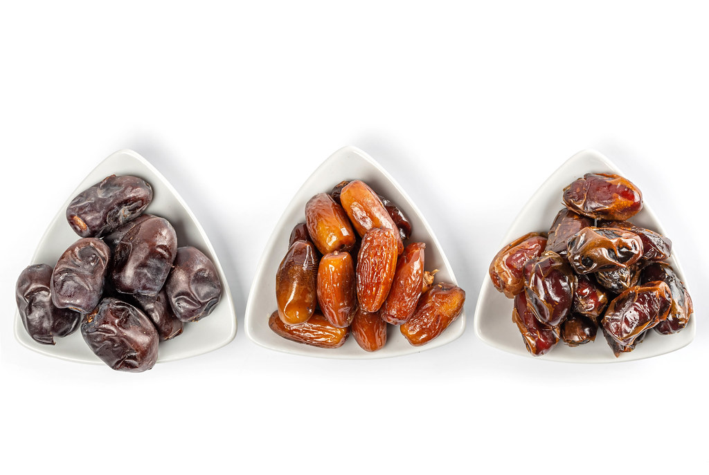 Different varieties of dates on white background, top view