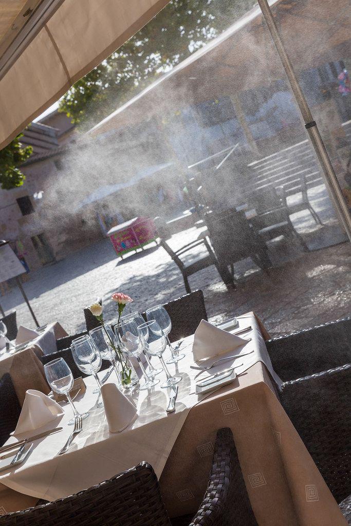 Dinner für vier Personen: gedeckter Tisch im Restaurant mit vier Gedecken und Blick auf den Platz
