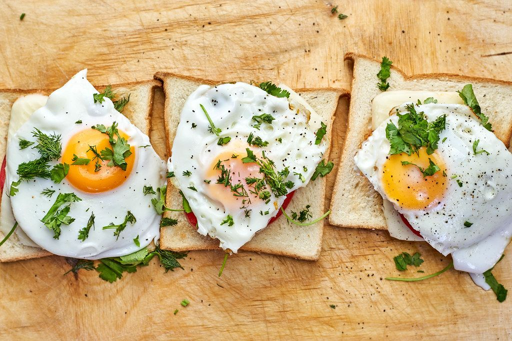 Directly above shot of fried eggs with toast and parsley on cutting board