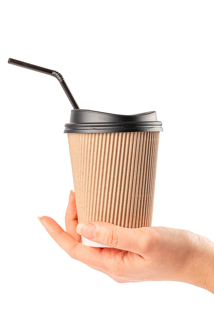 Disposable coffee cup with a lid and a straw in a woman