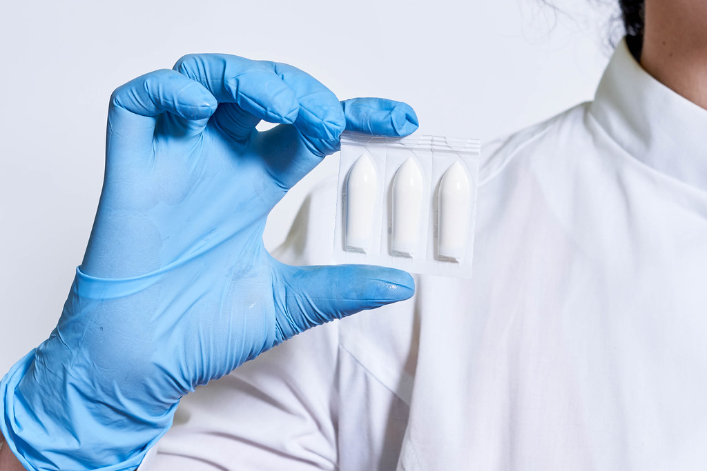 Doctor hand holds hemorrhoidal suppository