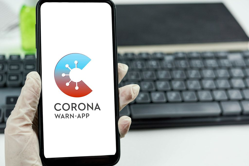 Doctor holding a smartphone with Corona warn-app that helps trace infection chains of SARS-CoV-2 or COVID-19 in Germany