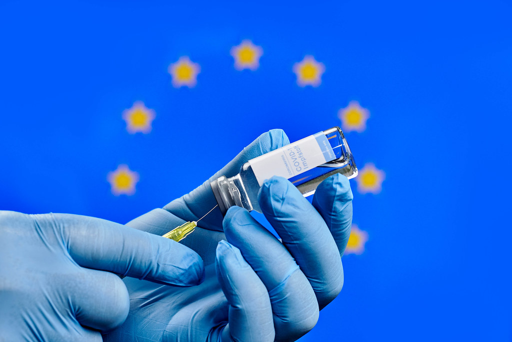 Doctor preparing Covid-19 injection against the European Union flag