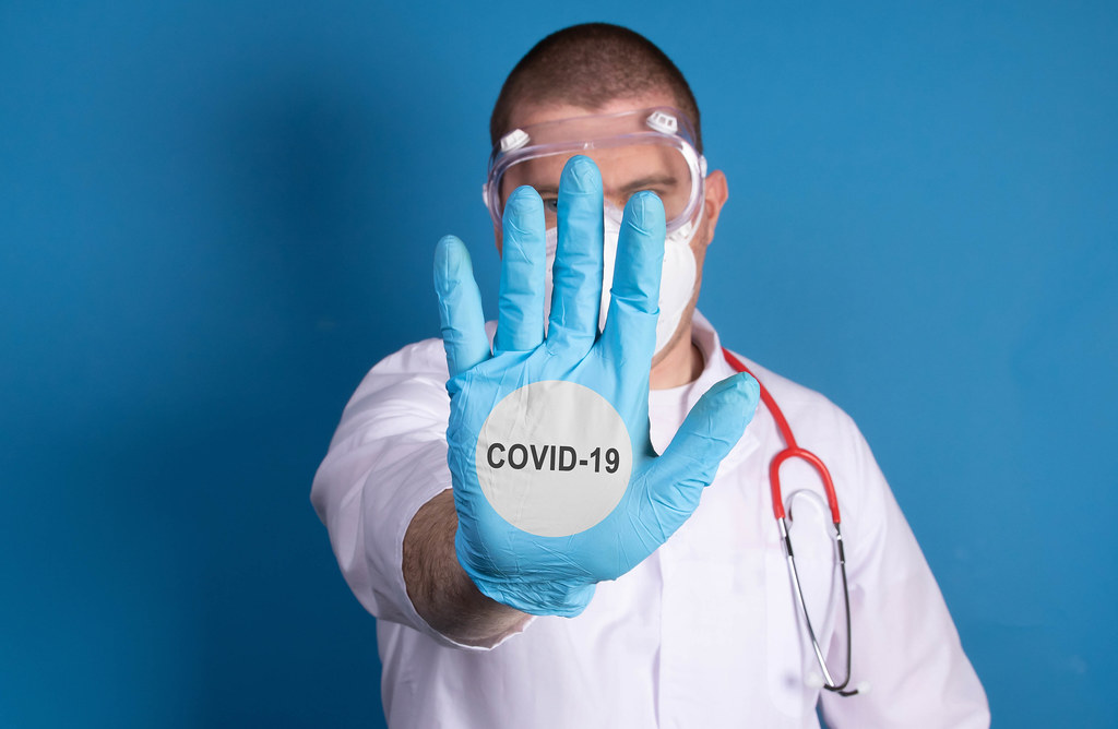 Doctor wearing protective gloves and Covid-19 text