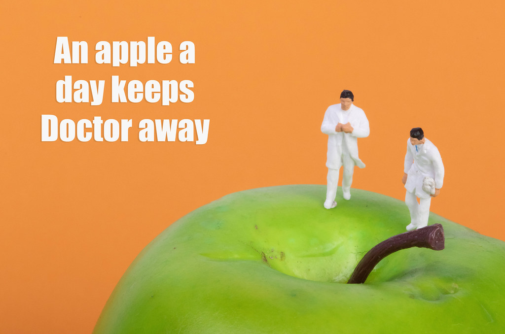 Doctors on apple with An apple a day keeps Doctor away text