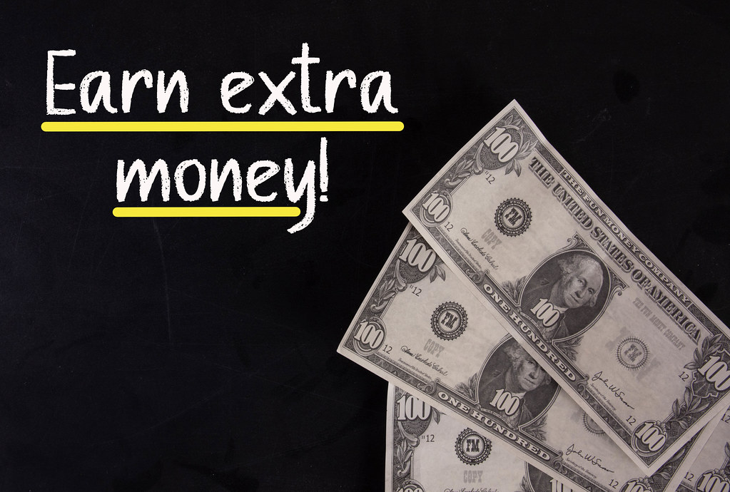 Dollar banknotes with Earn extra money text