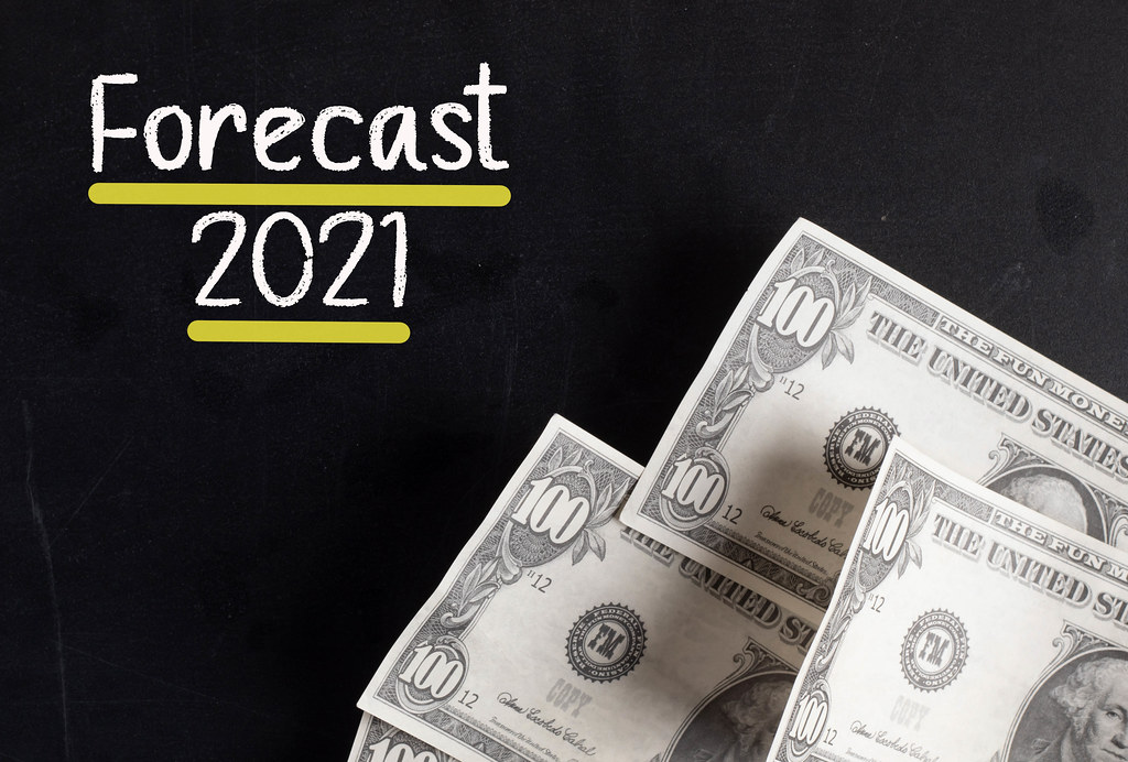 Dollar banknotes with Forecast 2021 text
