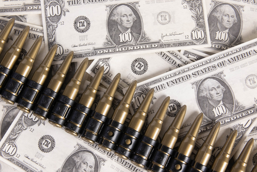 Dollar banknotes with rifle bullets