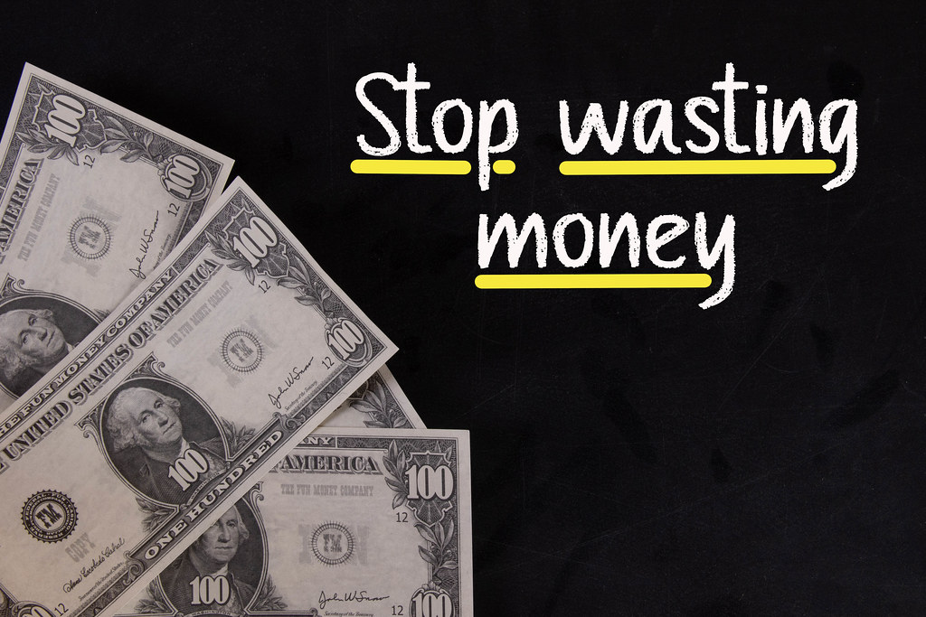 Dollar banknotes with Stop wasting money text