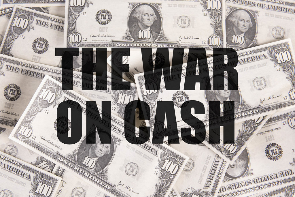 Dollar banknotes with The war on cash text