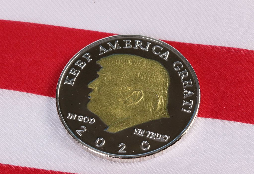 Donald Trump on a coin against American flag