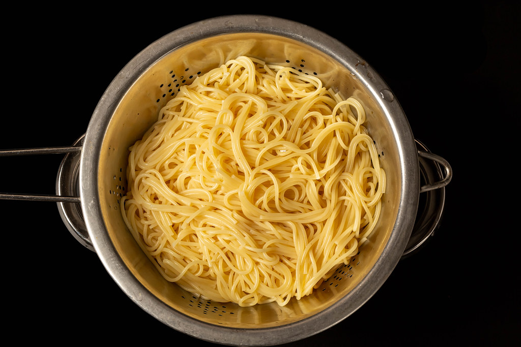 Draining hot, cooked spaghetti in a colander, top view