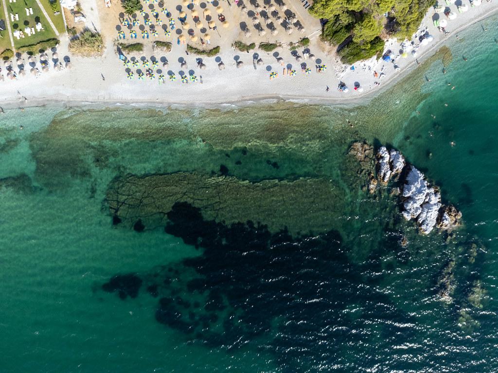 Draufsicht: der Strand Milia auf Skopelos mit türkisem Wasser und Stroh- und blau-gelben Sonnenschirmen