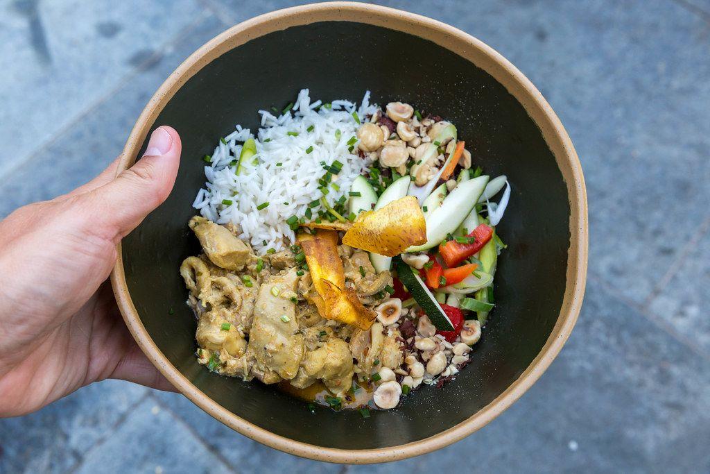 Draufsicht: Hand hält einen schwarzen tiefen Teller mit Curry-Landhuhn, Gemüse und Reis. Q11, Pollença