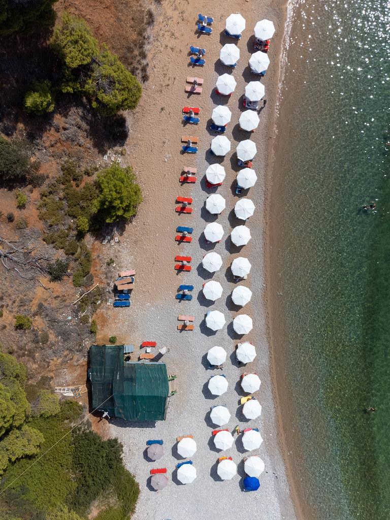 Draufsicht: Kokkinokastro Strand auf Alonnisos mit Reihen von weißen Sonnenschirmen