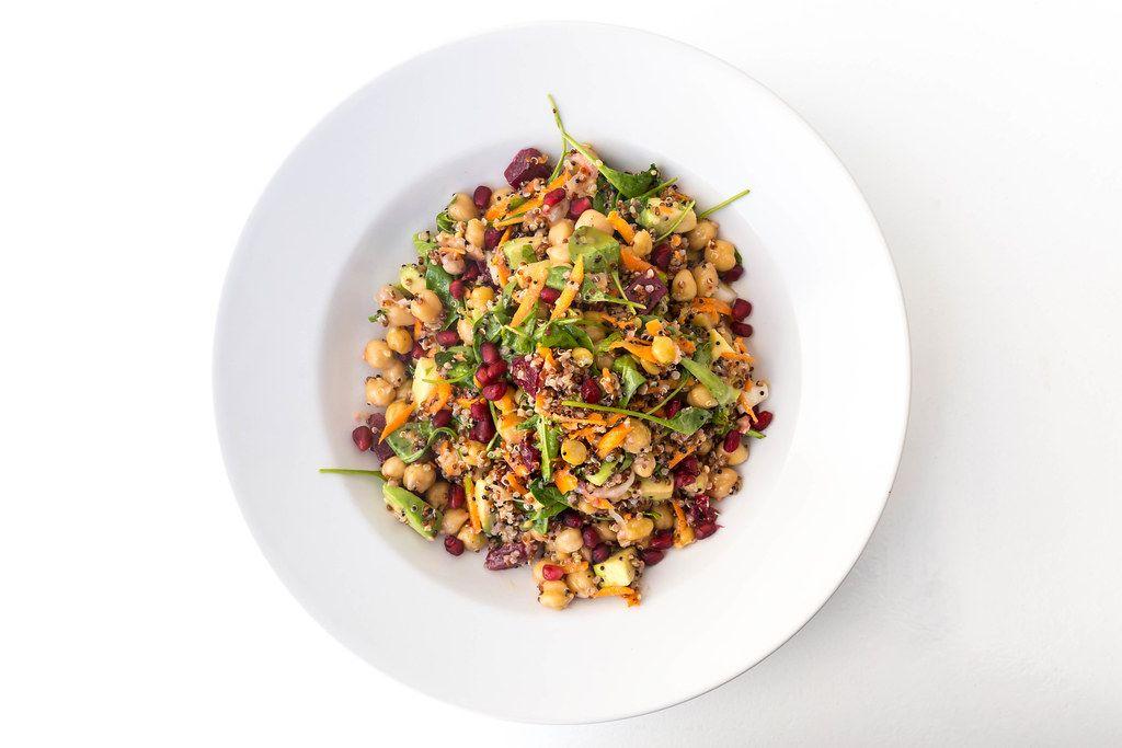Draufsicht: veganes Gericht mit Kichererbsen, roter Bete, Möhren, Avocado, Quinoa, Spinat und Kräutern