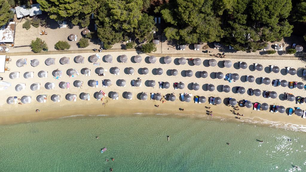 Draufsicht von Sonnenschirmen auf den traumhaften Strand von Koukounaries in Griechenland
