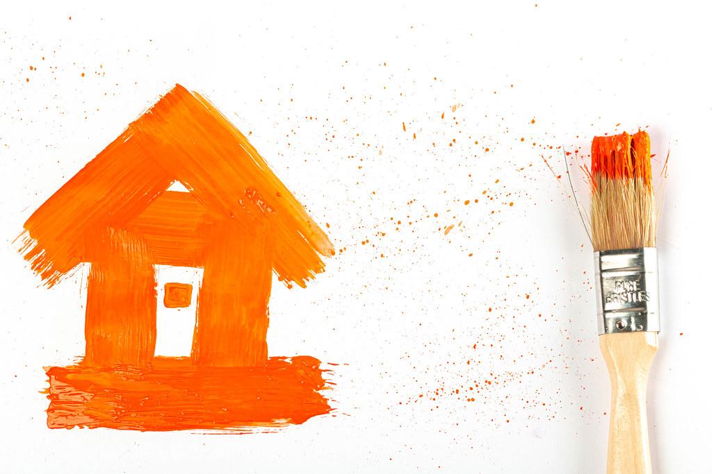 Drawn house with orange splashes and brush