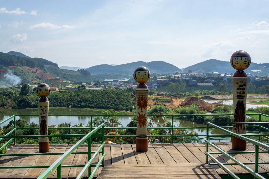 Drei Figuren in verschiedenen Größen auf einer Holz-Aussichtsplattform mit Dörfern, Bergen und einem See im Hintergrund in Da Lat, Vietnam