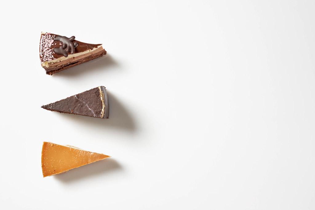Drei Portionen Torte aus der Konditorei vor weißem Hintergrund mit Platz für Text rechts