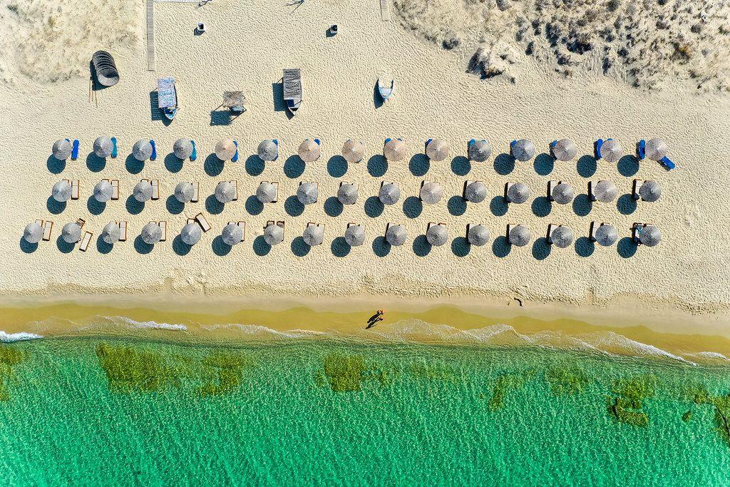 Drei Reihen Strandliegen mit Sonnenschirmen am schönen Strand von Plaka auf Naxos. Luftaufnahme