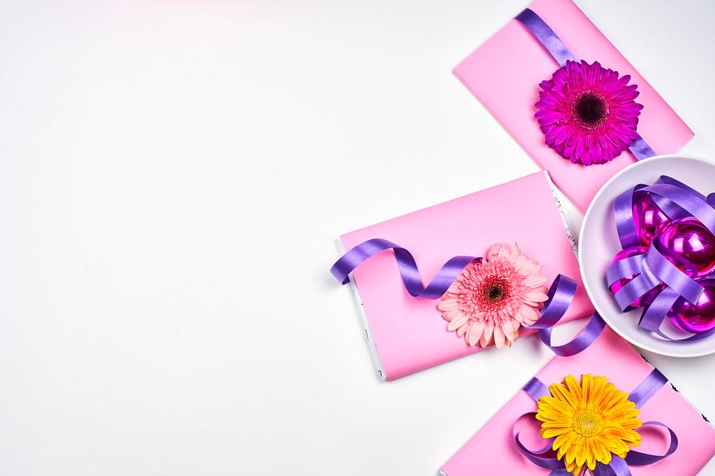 Drei rosa Geschenke mit Blumen, lila Schleife und Weihnachtskugeln mit Platz für Text links