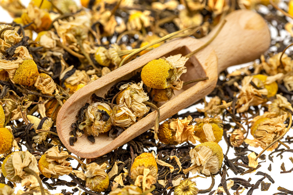 Dried chamomile flowers with black tea with wooden scoop